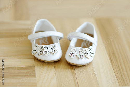 Cute little baby shoes on a floor