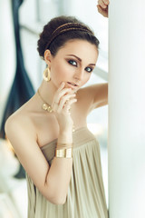 Portrait of beautiful woman in gold dress with arabic make up