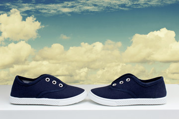 Blue sneakers on background cloudy sky