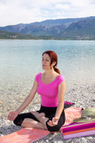 Woman meditating on a lakeshore. poster