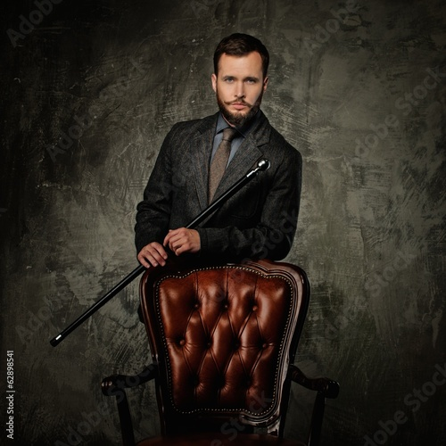 Handsome well-dressed man with stick near chair