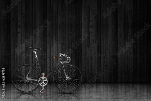 Deurstickers Fiets classic fixed gear bicycle on black wood stage