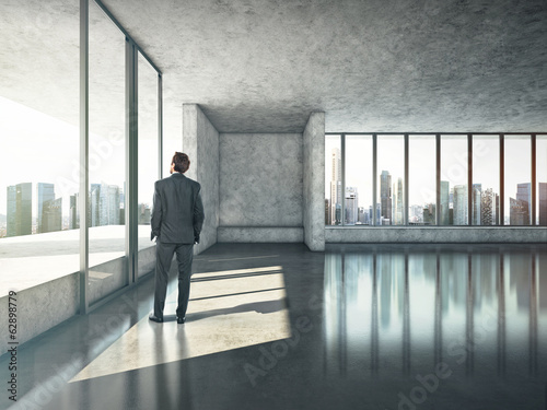 Businessman standing in sunny office