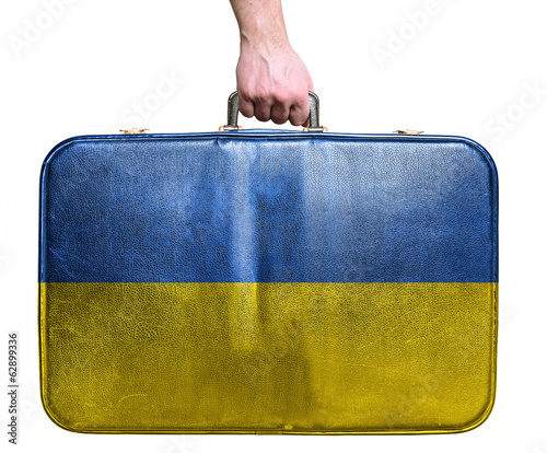 Tourist hand holding vintage leather travel bag with flag of Ukr