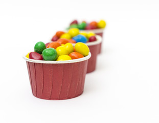 Isolated colorful candy in paper cup - selective focus
