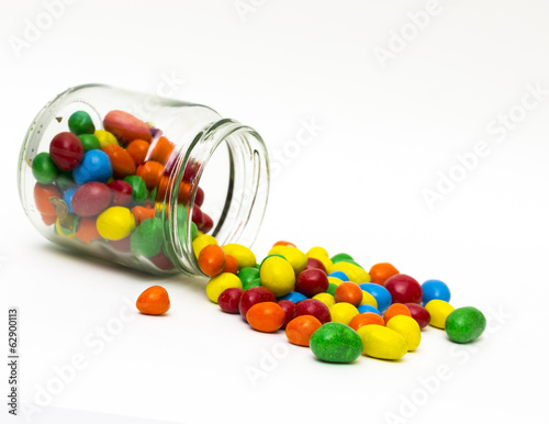 Isolated colorful candy out of jar on white background - selecti