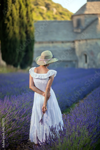 Young woman in lavender field looking to the medieval Abbey of S