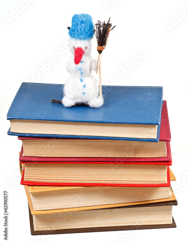 felt soft toy snowman on stack of books