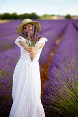 Young romantic woman standing in lavender field showing a bouqut
