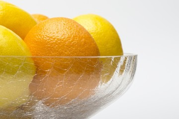 Oranges and lemons in glass bowl