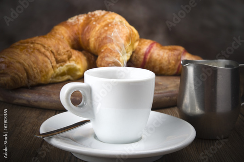 Hot coffee and fresh croissants on the wood table