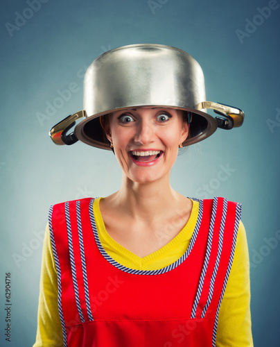 Portrait of happy housewife with sause pan on her head