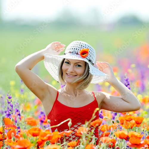 young beautiful woman on flower field in summer