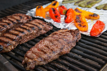 Steaks cooking on the grill and colorful peppers on background