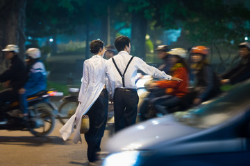 Young couple crossing busy street. Vietnam.