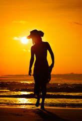 young woman silhouette on the beach in summer