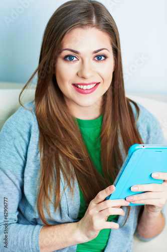 Young woman working with tablet pc, pad at home. Female model