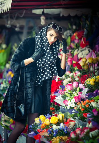 Beautiful brunette woman with gloves at florist shop