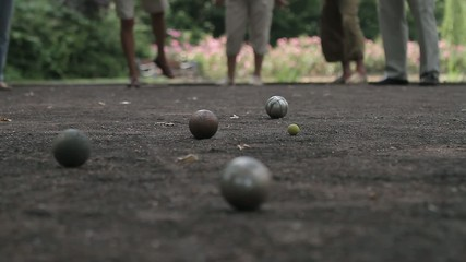 elderly people enjoying to play boules in a park, ball shooting