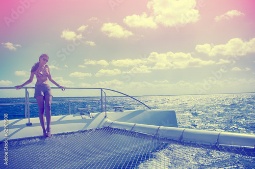 A woman holding a rail on a catamaran in the Caribbean Sea