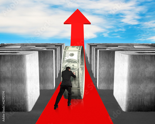 Man pushing money on growing red arrow through maze