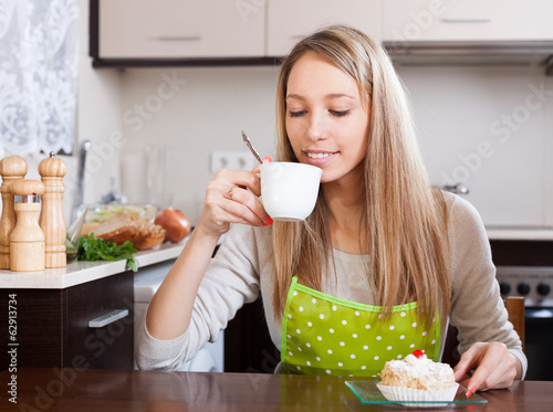 Housewife  drinking tea with cake
