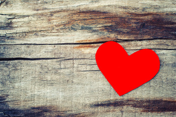 Red paper heart on grunge wooden background