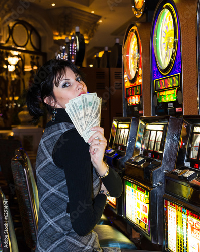 Lucky woman holding money in casino