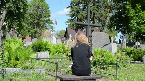 Widow woman near soldier father grave. Lithuania national flag