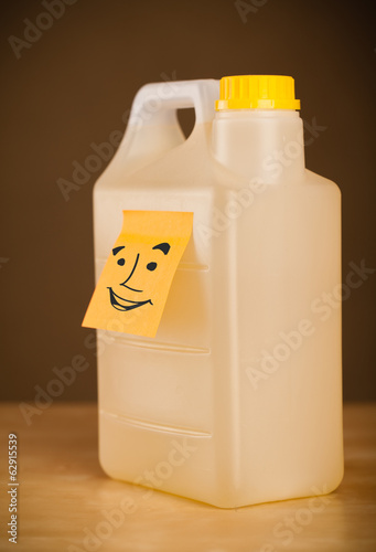Post-it note with smiley face sticked on a can