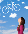 Young girl looking at bicycle clouds on blue sky