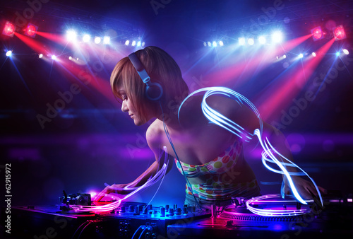 Disc jockey girl playing music with light beam effects on stage - 62915972