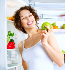 Diet. Beautiful young woman near the fridge with healthy Food