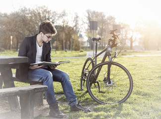 teenager with bicycle reading book in park