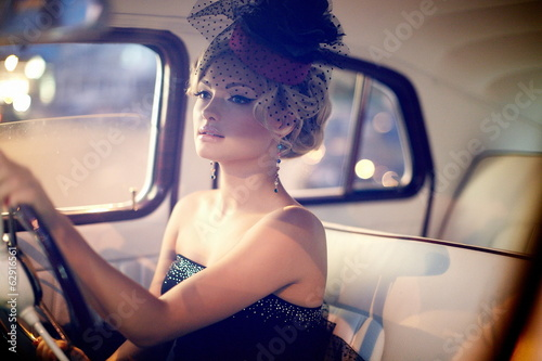 fashion stylish blond girl in retro style sitting in old car