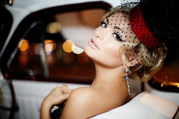 fashion stylish blond girl in retro style sitting in old car