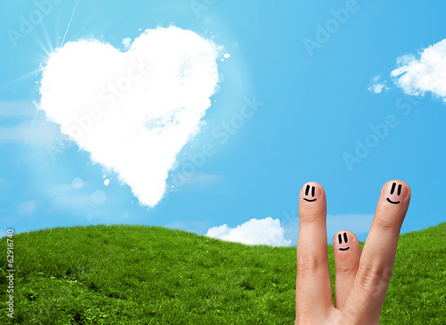 Happy smiley fingers looking at heart shaped cloud