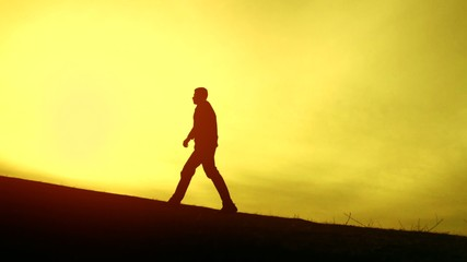 Businessman Walking Up a Hill toward top sun success concept