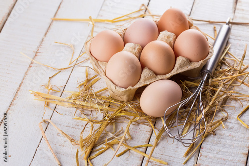 Chicken eggs on wooden background.