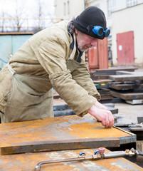 Welder worker measuring and marking steel sheet for cutting