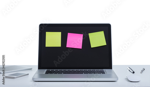 Laptop computer with adhesive note on screen