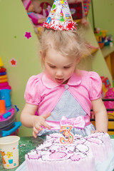 Little girl with birthday cake on her birthday party