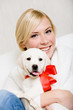 Woman embracing white white puppy with red ribbon on the neck