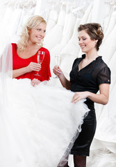 Two girls drink champagne while discussing wedding gown
