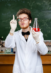 Mad professor in rubber gloves  works in his laboratory