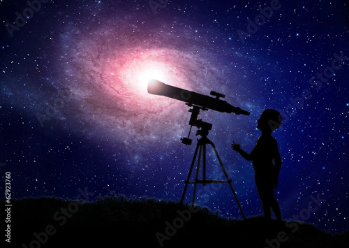 Boy looking through a telescope
