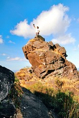 a man stand on top of the rock under blue sky
