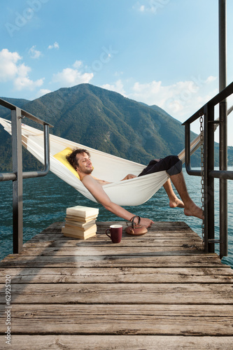 canvas print picture portrait of young man on the dock of Lake