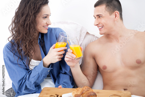 beautiful young couple having breakfast in bed together