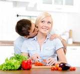 Man kisses lady while she is cooking